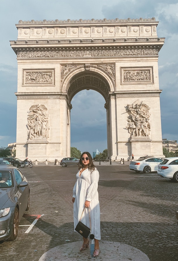 Woman in a flowy white dress holding a black purse on a chain standing in front of the Arc de Triomphe.