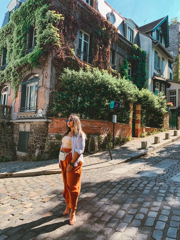A woman in a flowy white button-up, nude crop top, and baggy orange pants stands on a cobblestone street in Paris.