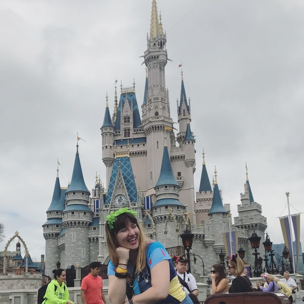 A woman smiles and poses in front of Cinderella's castle at Disney World.