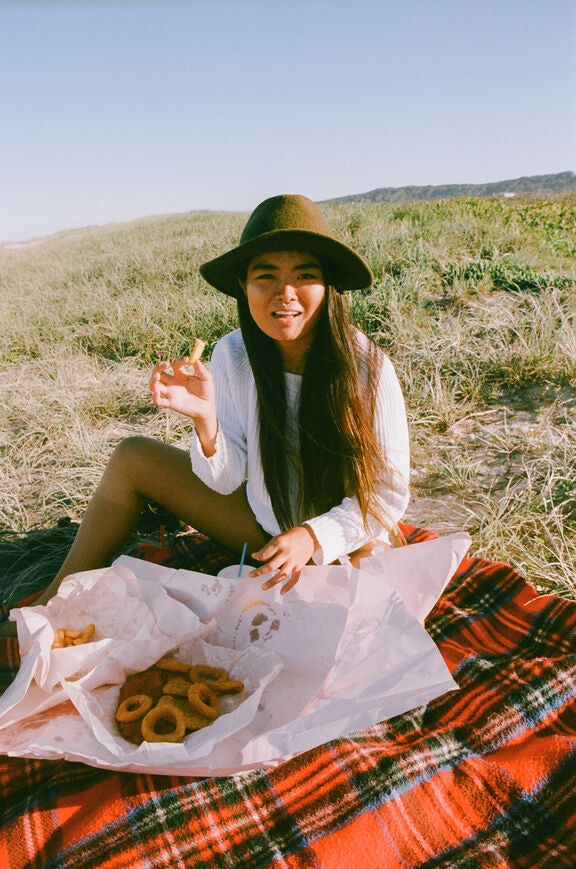 A woman eats fish and chips on a red plaid picnic blanket on a green hill in the fall.