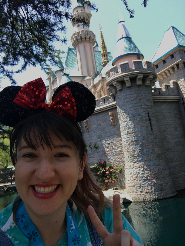 A woman smiles, holds up a peace sign, and takes a selfie in front of the castle at Disneyland with sequined Minnie ears on her head.