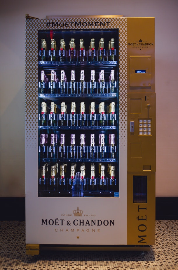 The Moët & Chandon vending machine In NYC has two kinds of champagne in it and a gold and white exterior.