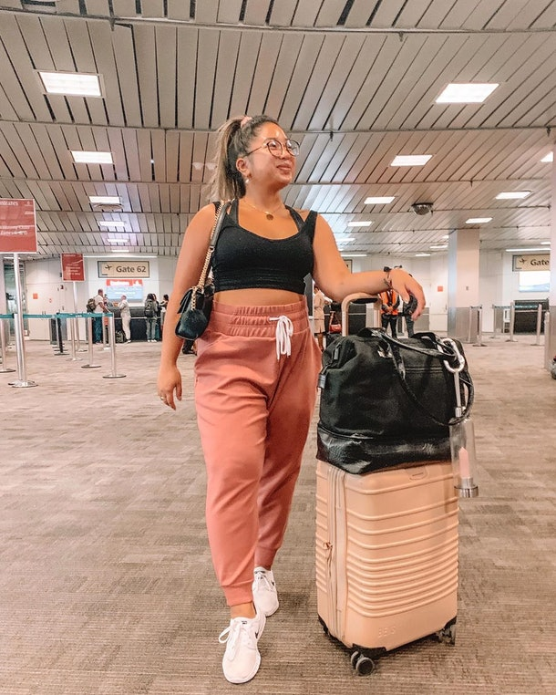 A woman in black crop top and pink sweatpants with carry-on luggage waits at an airport gate.