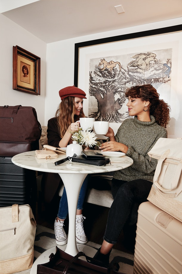 Two friends clink their coffee mugs together at a café with luggage and bags from Shay Mitchell's BÉIS winter collection next to them.