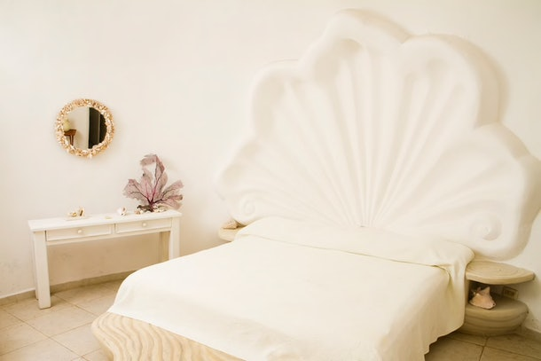 A bedroom in the Seashell House on Airbnb has a shell headboard and decorative mirror.