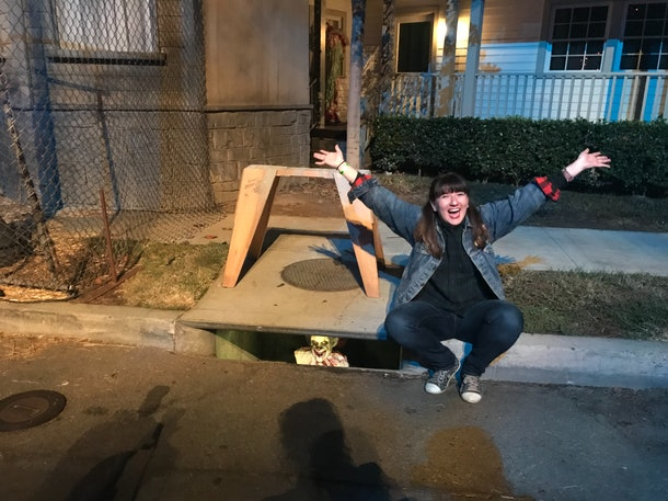 A woman poses with Pennywise the clown from the horror movie, 'IT', in a storm drain for Halloween.
