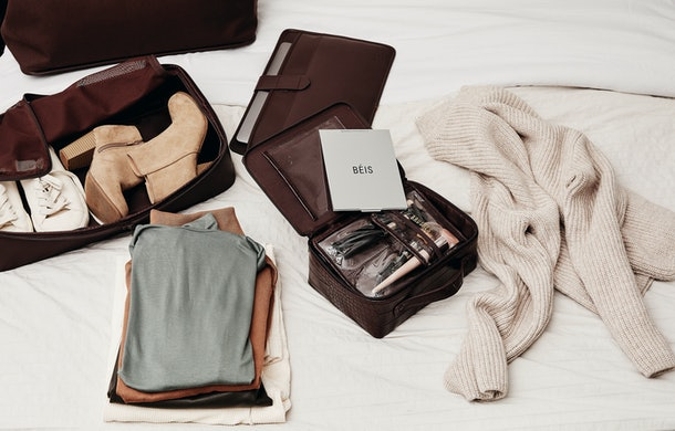 Winter clothes, shoes, and beauty products are laid out on a white bed and packed into espresso-colored products from Shay Mitchell's BÉIS winter collection.