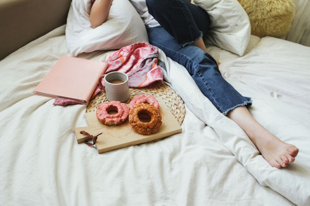 A girl lays in a comfy bed with a plate of pumpkin doughnuts, a mug of coffee, and a pink notebook.