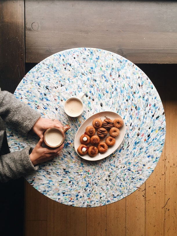 A woman sits at a multicolor table with a plate of pumpkin doughnuts and lattes.