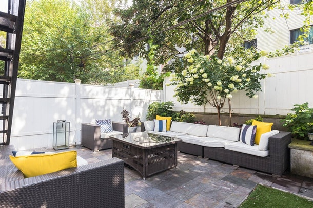 An outdoor patio features black wicker furniture that's topped with white cushions, accented with solid yellow and blue and white striped pillows at a pet-friendly Airbnb in Brooklyn.