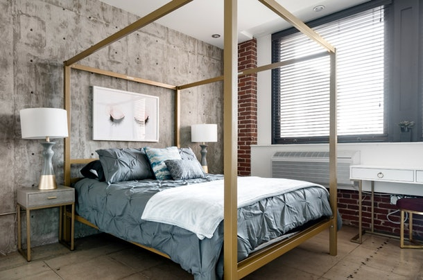 A queen bed in an industrial-looking room covered in slate gray bedding surrounded by a gold canopy bed frame.