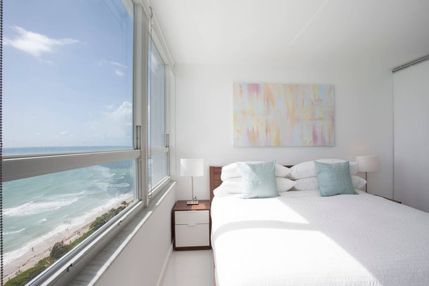 A room with a white queen-sized bed and wooden bedside tables overlooks the beach and an ocean.