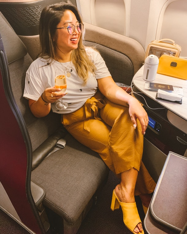 A woman wearing a white T-shirt, brown pants, and yellow mule heels sits in a business class plane cabin holding a glass of champagne.