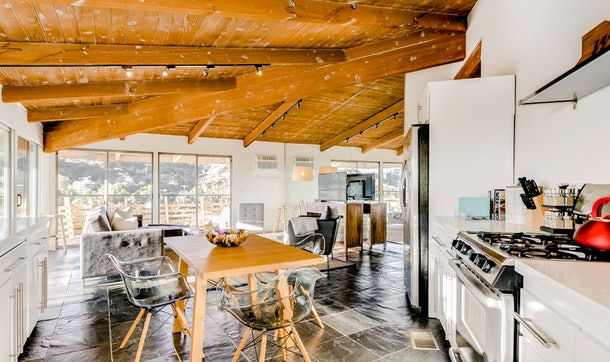 A giant open loft, with a dining table, kitchen and living room visible, with floor to ceiling windows overlooking the Hollywood Hills.