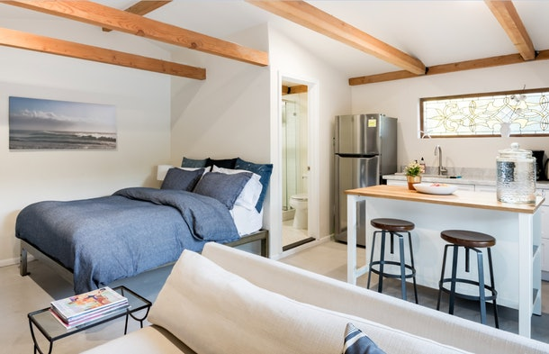 An open floor plan studio apartment in LA on Airbnb showcases a queen bed, a counter with two stools, part of a white couch, and a glimpse into the bathroom.