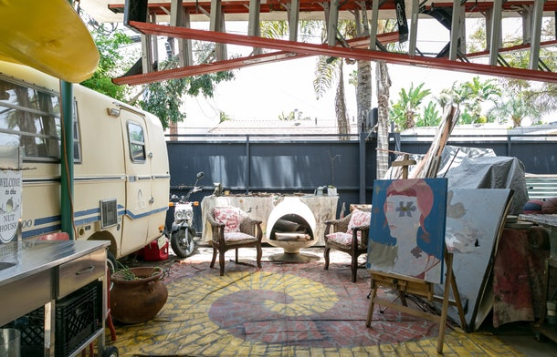 An outdoor art studio with murals and paintings scattered around and a vintage camper on the left.