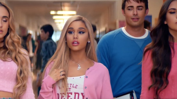 Ariana Grande dresses as Regina George from 'Mean Girls' with a pink cardigan and white tank top on.