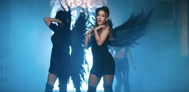 Ariana Grande poses in a black bodycon mini dress and thigh-high boots, with feathered angel wings on her back.