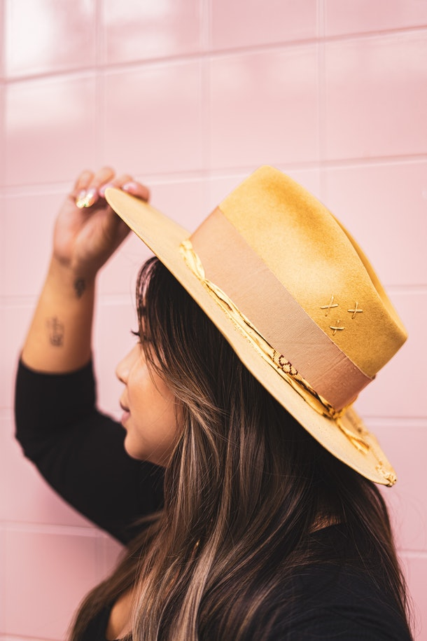 A profile of a woman with dark hair wearing a mustard yellow felt hat against a pink tile wall.