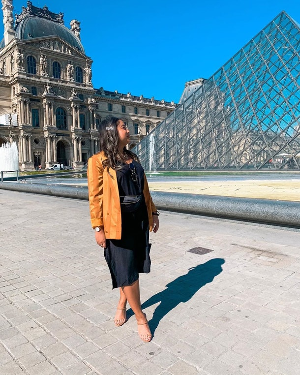 """A woman in a black dress and yellow blazer poses in front of the Louvre Pyramid with her head turned to the side to show off her hair clip that says """"Glam."""""""