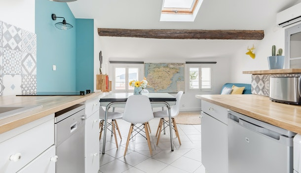 A comfortable apartment in Toulon has a bright kitchen with a single blue wall and wood details.