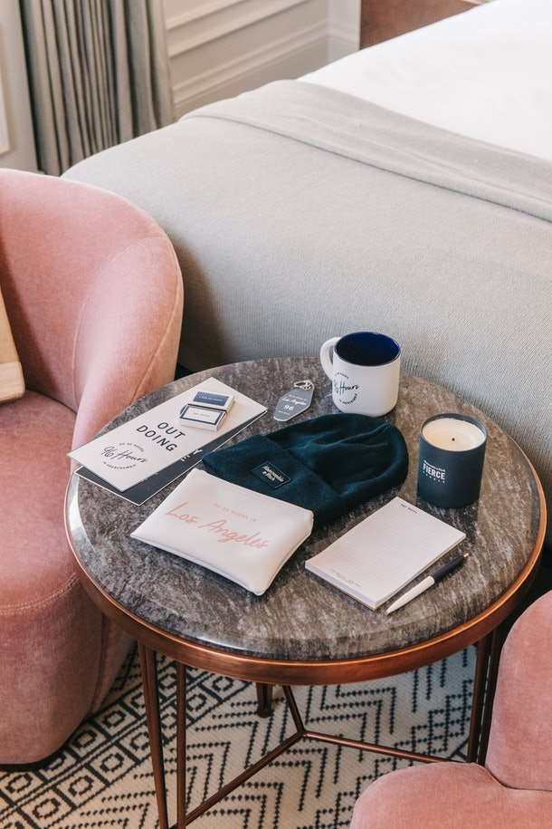 A dark marble coffee table with staycation products — like an itinerary, beanie, candle, toiletry pouch, and more — sitting on top of it.