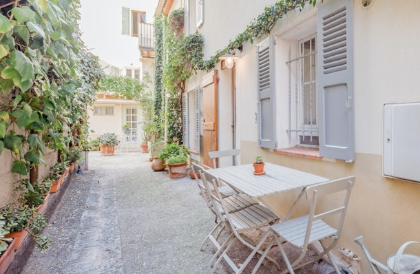 The entrance to a townhouse in Antibes is decorated with a table and chairs and lots of greenery.