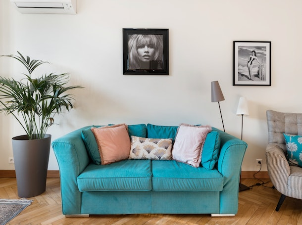 The living room of an apartment in Nice has a bright blue couch with pillows and stylish artwork.