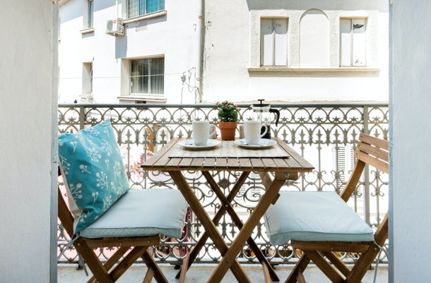 The balcony of an apartment in Antibes has a table with two chairs and is a great spot for enjoying breakfast.
