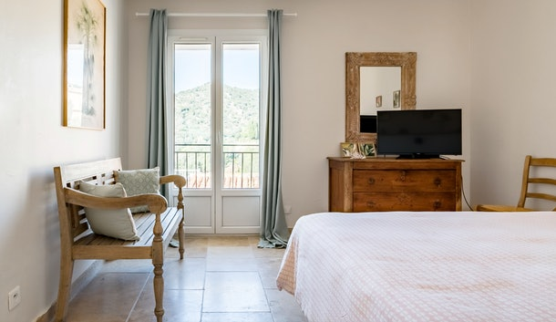 A bedroom in an apartment in Bormes-les-Mimosas is cozy and made for a couple's getaway.
