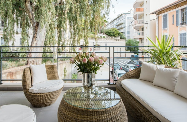 A luxe apartment in Cannes has a balcony with plush white couches, roses, and lots of greenery.