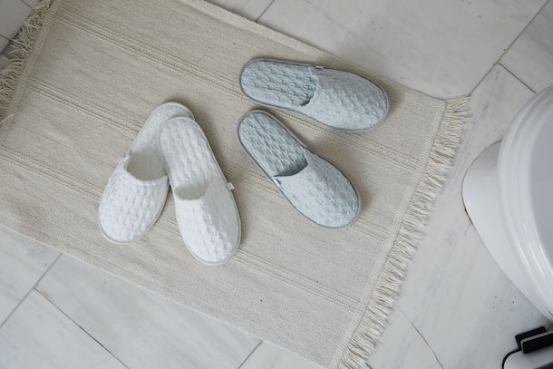 Two pairs of cozy slippers on a tile floor with a rug is something you may experience in the Allswell tiny home.