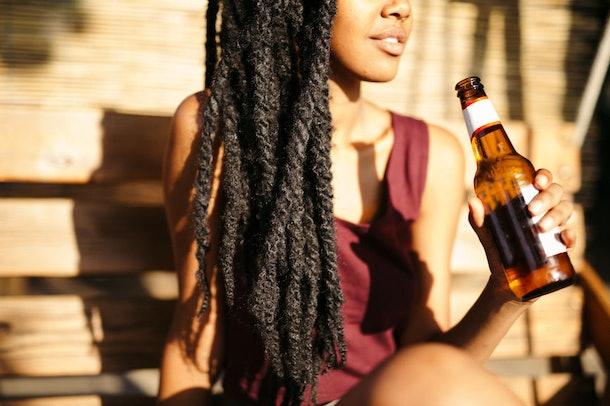 Une femme est assise au soleil avec une bouteille de bière à la main.