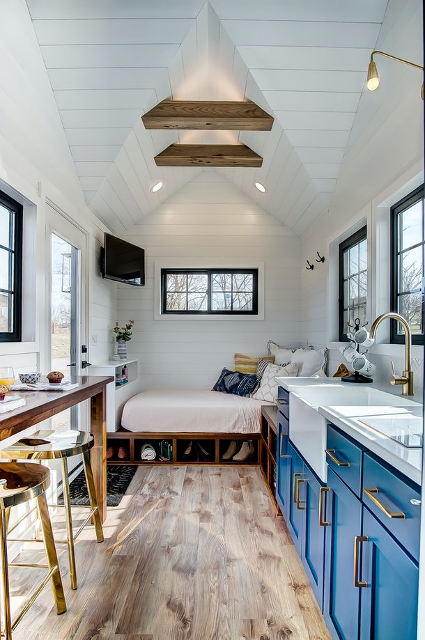 One side of the Allswell tiny home has a bed and lots of windows.