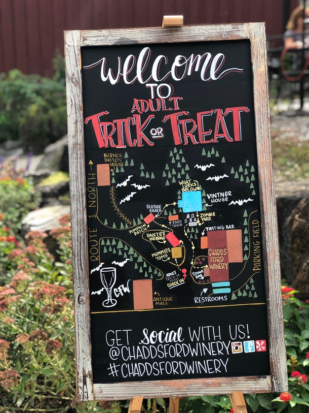 A chalkboard sign at Chaddsford Winery tells guests where to stop for wine and treats during their Adult Trick-or-Treat event.