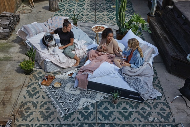 A group of friends is hanging out on Allswell mattresses with snacks.