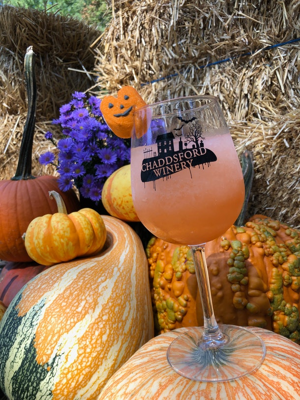 A wine glass filled with a drink sits in a pumpkin display at Chaddsford Winery's Adult Trick-or-Treat event.
