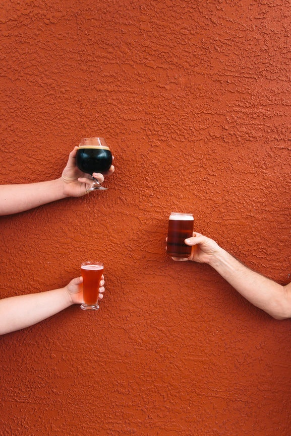 Three people holding up glasses of beer against an orange wall is the perfect post to pair with pumpkin beer captions.