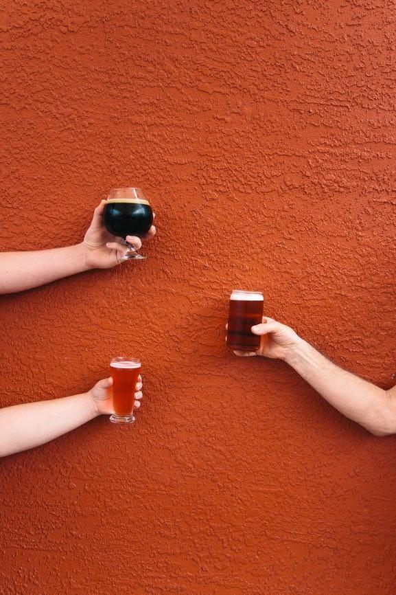 Trois personnes brandissant des verres de bière contre un mur orange constituent le poste idéal pour accompagner les légendes de la bière citrouille.