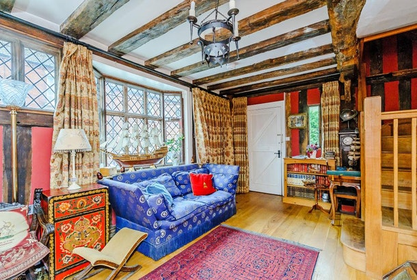 A living room features a bright blue couch, medieval decor, a high ceiling, and long curtains.