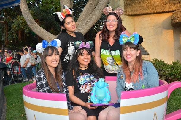 A group of women sit in a pink tea cup like the ride at Disneyland.