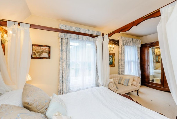 A beautiful vintage bed is next to a neutral-colored couch and window with light pouring through into the bedroom.