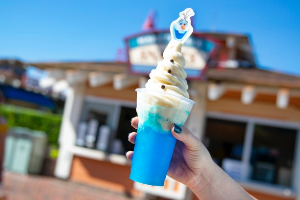 A woman's hand holds up the Olaf Dole Whip Slushy with Olaf from the movie 'Frozen 2' on top.