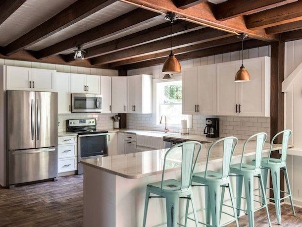 The kitchen of a house in Kennebunkport, Maine has teal chairs and a charming, rustic style.