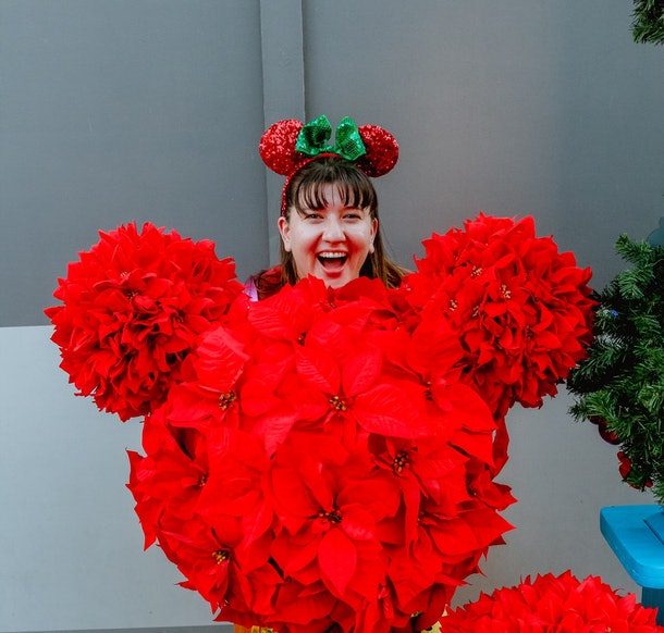 A woman stands behind a poinsettia flower bush shaped like Mickey Mouse, while wearing holiday Minnie ears at Disney.