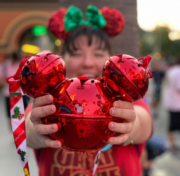 A woman holds a shiny red Mickey Jingle Bell Sipper that's available at Disney for the holidays out in front of her.