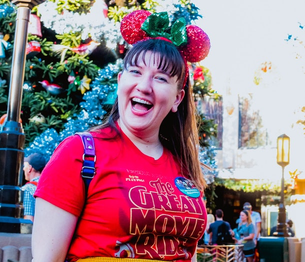 A woman wearing a holiday Disney button and festive Minnie ears smiles in front of a Christmas tree at California Adventure.