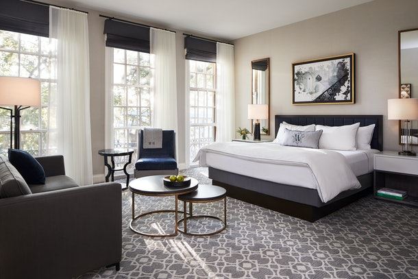 A modern hotel room is decorated with white, black, and gray decor at The Whitney in Boston.