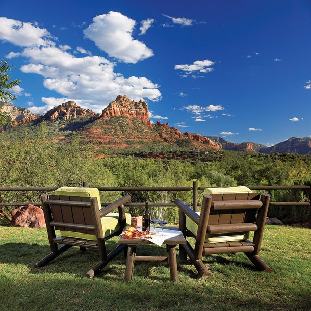 Two wooden lawn chairs and a matching table are on a lawn overlooking red rock mountains in the distance at L'Auberge de Sedona.