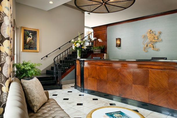 A luxe hotel lobby with a glossy wooden reception desk, marble floors, and a black staircase leading up to a second level at King Charles Inn.